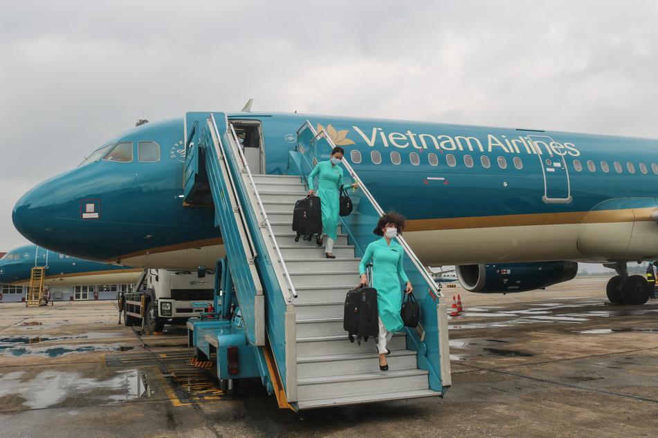Besatzungsmitglieder von Vietnam Airlines, die Mundschutzmasken tragen, gehen am internationalen Flughafen Noi Bai mit Koffern in der Hand von Bord.