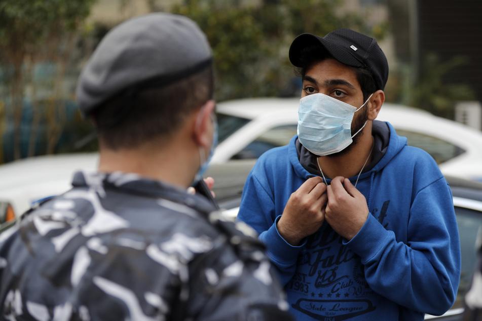 Libanon: Ein Autofahrer mit Mundschutz diskutiert mit einem Polizisten, nachdem er eine Geldstrafe bekommen hat. (Archivbild)