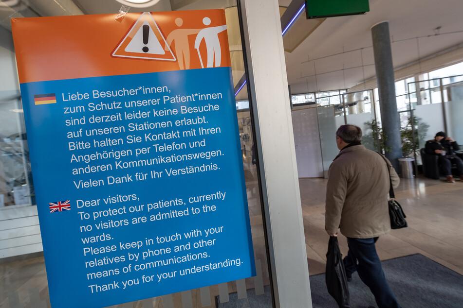 """Ein Hinweisschild für Besucher ist im Eingangsbereich des Krankenhaus """"Recht der Isar"""" in München angebracht."""