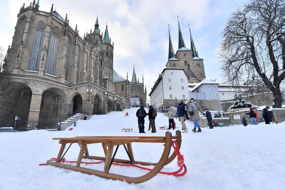 Rodeln in der Innenstadt: Auf dem Erfurter Domplatz vor dem Mariendom und der Severikirche machen Familien und Kinder das Beste aus dem Winterwetter.
