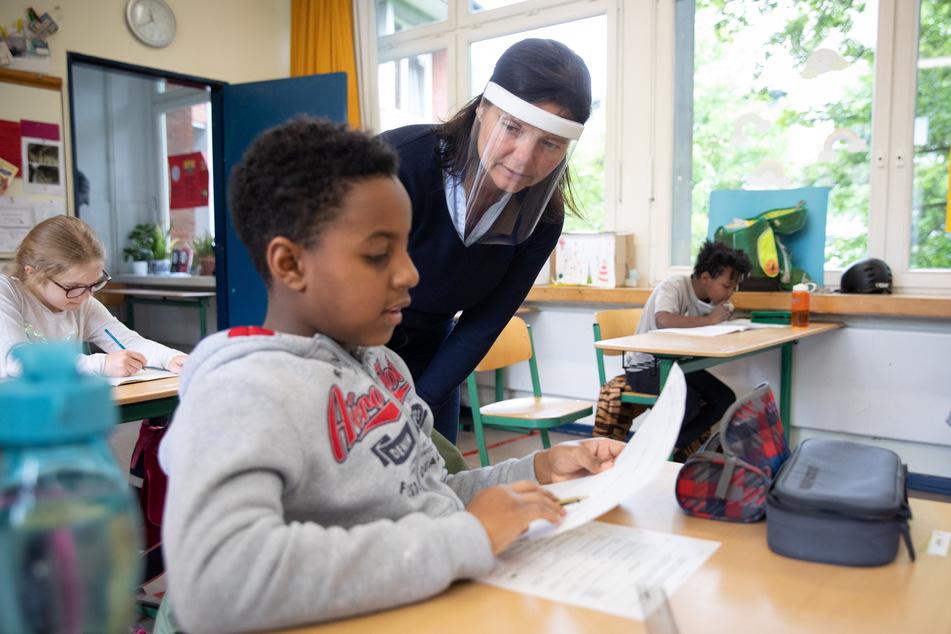Annegret Philipp, Lehrerin für Mathematik und Englisch, unterrichtet Schülerinnen und Schüler einer 4. Klasse der Hamburger Grundschule Wielandstraße und trägt dabei einen Gesichtsschutz.