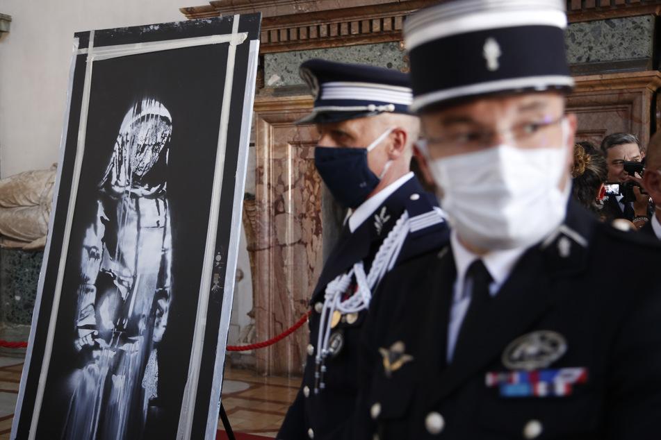 Die sogenannte Banksy-Tür, die von dem britischen Streetart-Künstler Banksy stammen soll, steht während einer symbolischen Übergabe von Italien an Frankreich in der französischen Botschaft.