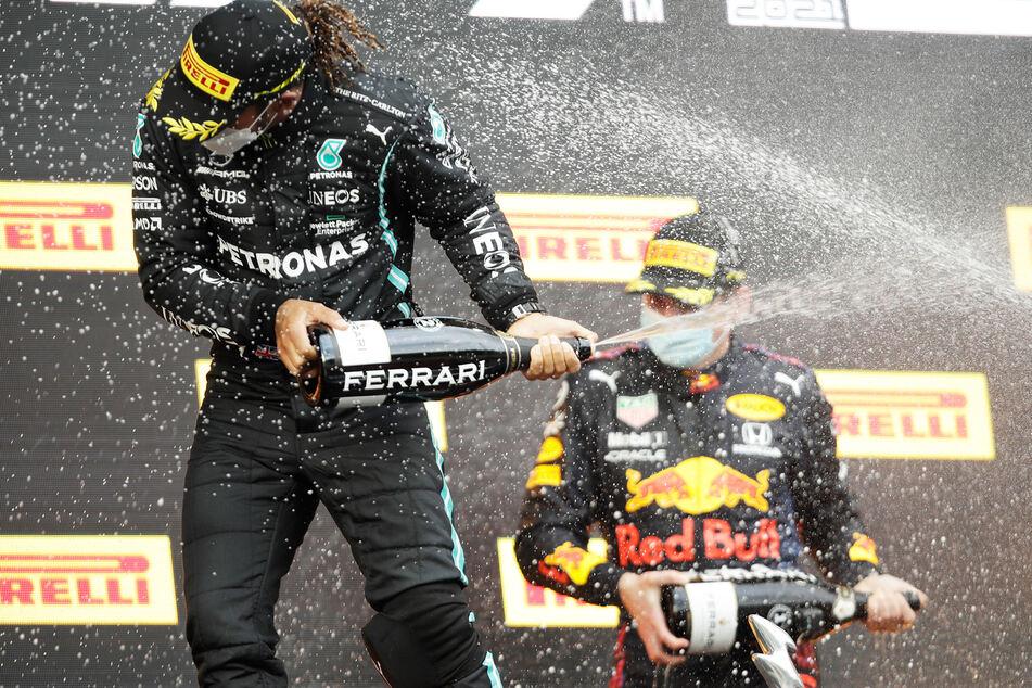 Max Verstappen (r.) feiert seinen ersten Saisonsieg neben dem Zweitplatzierten Lewis Hamilton.