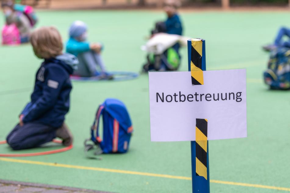 """Schüler warten hinter einem Schild mit der Aufschrift """"Notbetreuung"""", das auf dem Schulhof der Klenzeschule in München befestigt ist."""