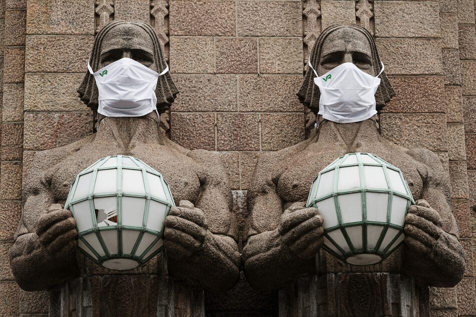 Die Statuen am Hauptbahnhof von Helsinki haben einen Mundschutz erhalten.