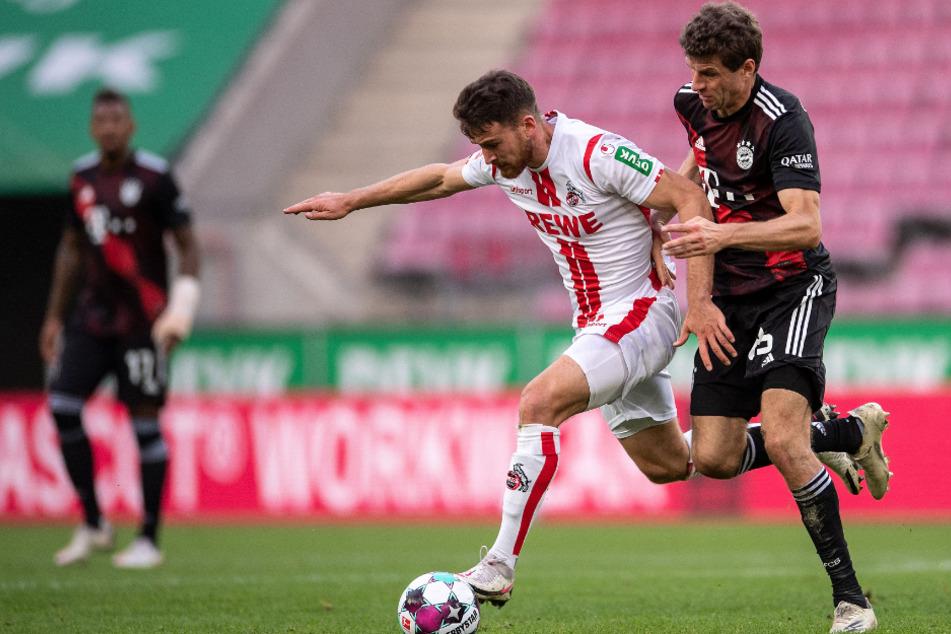 Kölns Salih Özcan (l.) und Bayerns Thomas Müller kämpfen um den Ball.