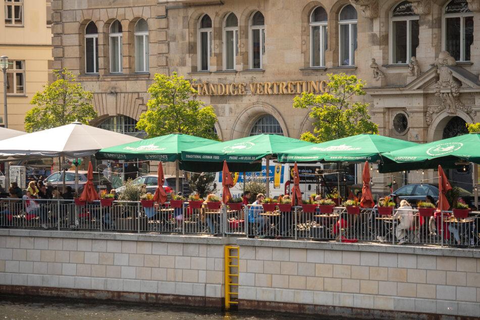 Menschen sitzen in den Außenbereichen von Cafés und Resataurants an der Spree.