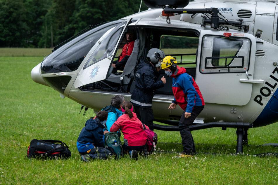 Einsatzkräfte der Polizei und der Bergwacht lassen die erste Familie, die sie von der Höllentalangerhütte gerettet haben, im Tal aus dem Hubschrauber.