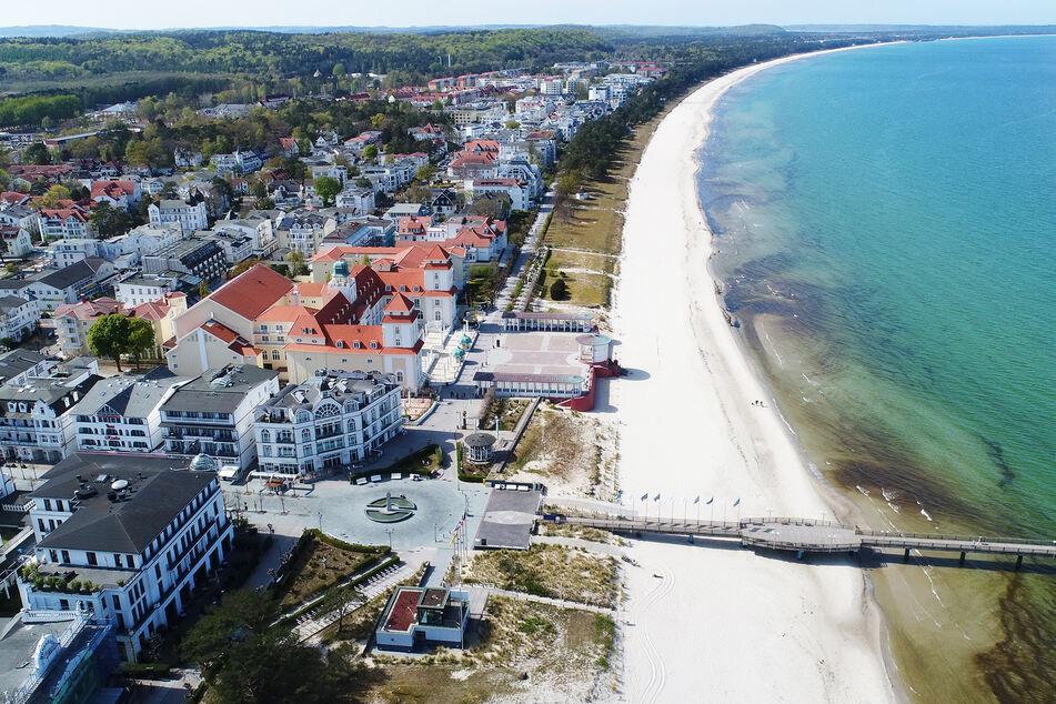 Einzelne Spaziergänger gehen am Strand im Ostseebad Binz auf der Insel Rügen.