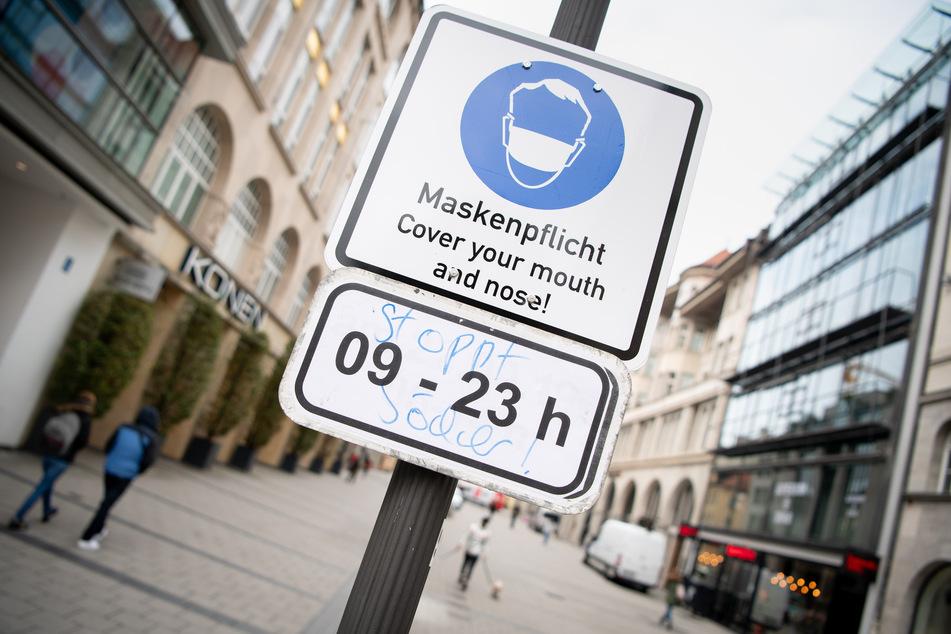 """Ein Schild mit der Aufschrift """"Maskenpflicht - Cover your mouth and nose! - 09 - 23h"""" weist in der Innenstadt von München auf die Maskenpflicht zwischen 9 Uhr morgens und 23 Uhr abends hin."""