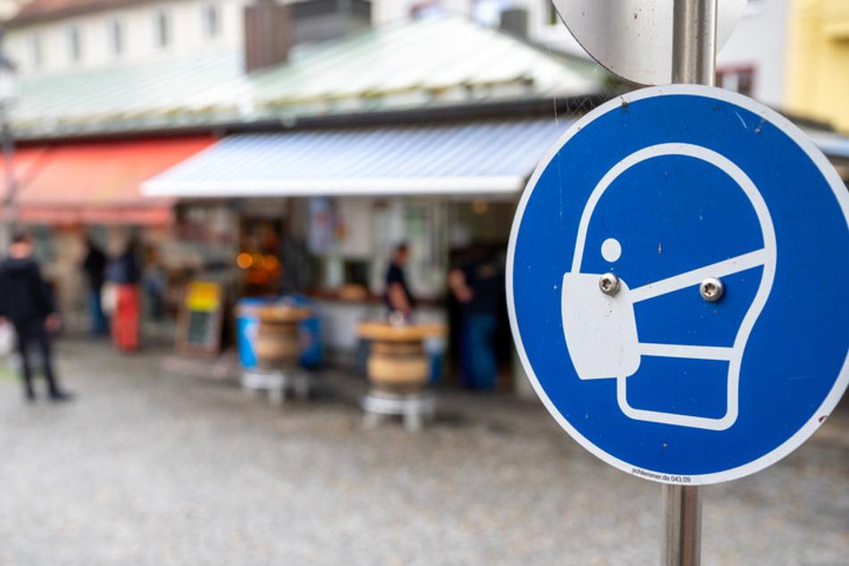 Ein Schild fordert am Münchner Viktualienmarkt zum Tragen einer Mund- und Nasen Bedeckung auf.