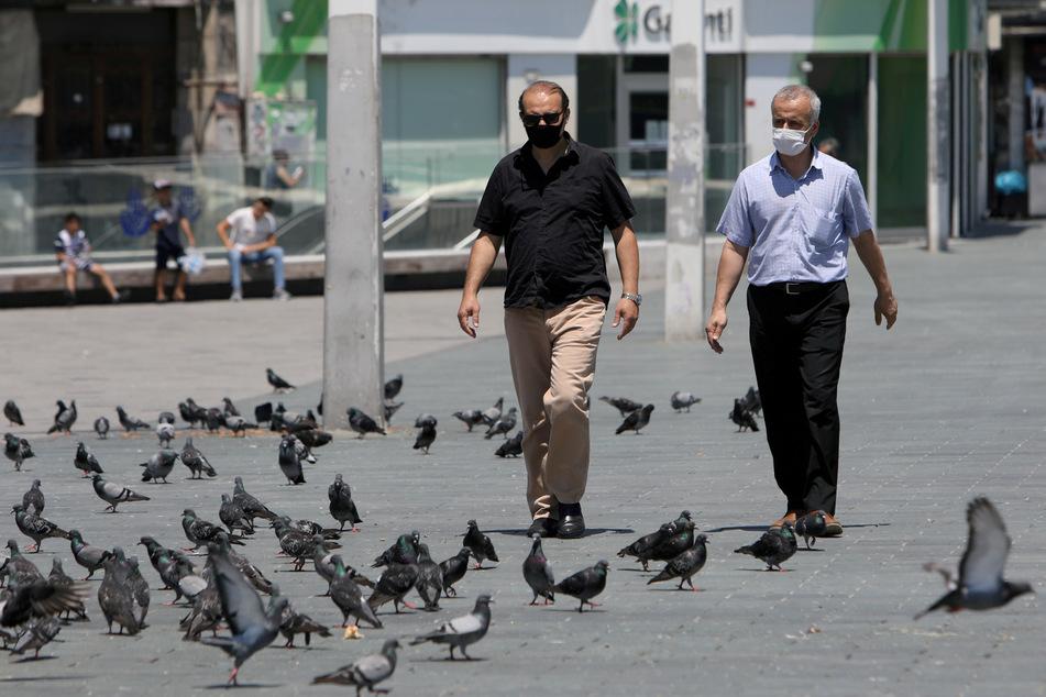 Passanten mit Mundschutz gehen auf einer Straße an Tauben vorbei. Am Samstagmittag darf das nicht jeder.
