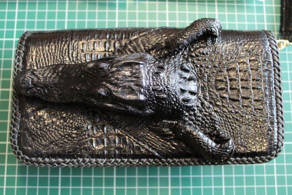 Unter anderem fand sich in dem Paket eine Brieftasche aus Krokodilleder, auf dem auch der Kopf eines kleinen Reptils verarbeitet wurde.