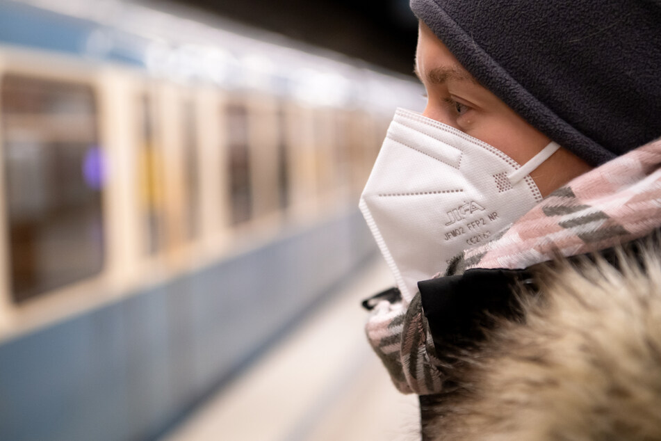 Eine Frau mit FFP2-Maske wartet in einer U-Bahnstation auf die Bahn. In Bayern gilt vom kommenden Montag an eine Pflicht zum Tragen von FFP2-Masken im öffentlichen Nahverkehr und im Einzelhandel.