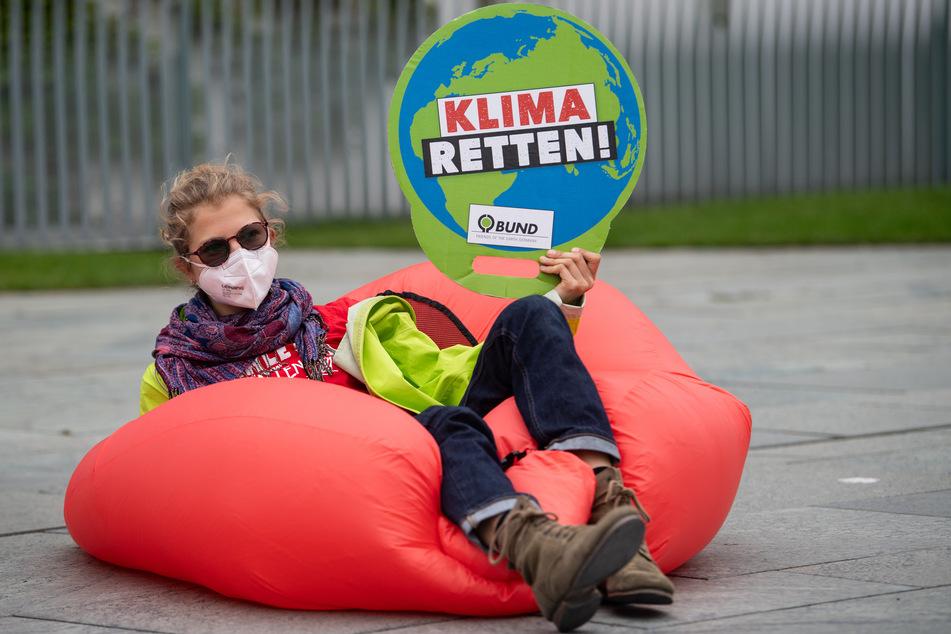 """Eine Umweltaktivistin hält bei einer Demonstration für mehr Klimaschutz vor dem Bundeskanzleramt ein Plakat mit der Aufschrift """"Klima retten!""""."""