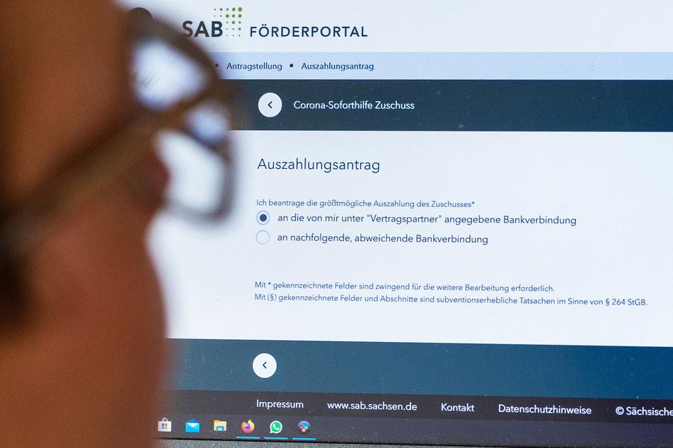 Eine Frau füllt am Computer auf der Internetseite der Sächsischen Aufbaubank einen Antrag auf Corona-Soforthilfe Zuschuss aus.