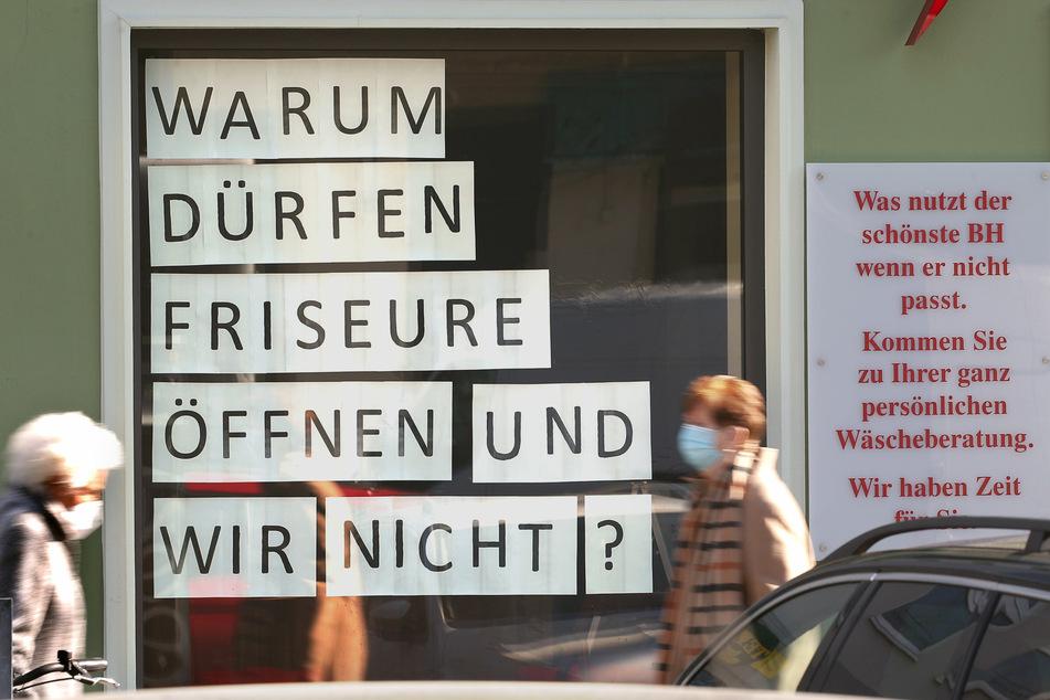 Frauen gehen im Bezirk Köpenick an einem geschlossenen Geschäft für Miederwaren vorbei, dessen Inhaber auf Plakaten ihren Unmut über Geschäftsöffungen kund tun.