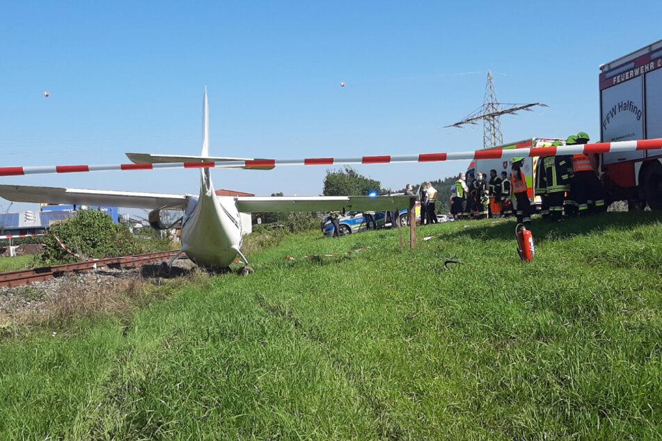 Retter stehen an der Unfallstelle neben dem Ultraleichtflugzeug.
