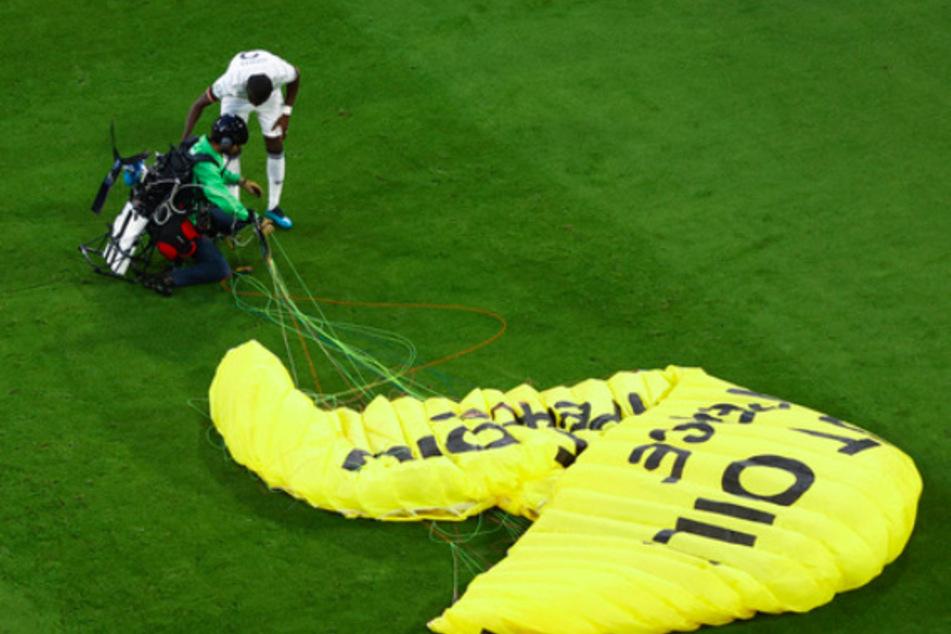 Antonio Rüdiger (Deutschland) spricht mit dem Greenpeace-Aktivist auf dem Spielfeld.