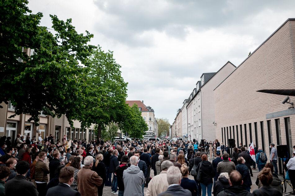 Hunderte stehen auf dem Platz vor der Synagoge.