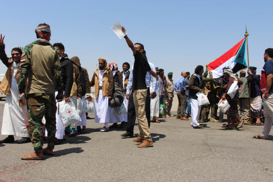 Yemeni prisoners who were kidnapped by Houthi rebels walk across an airport runway in the city of Aden.