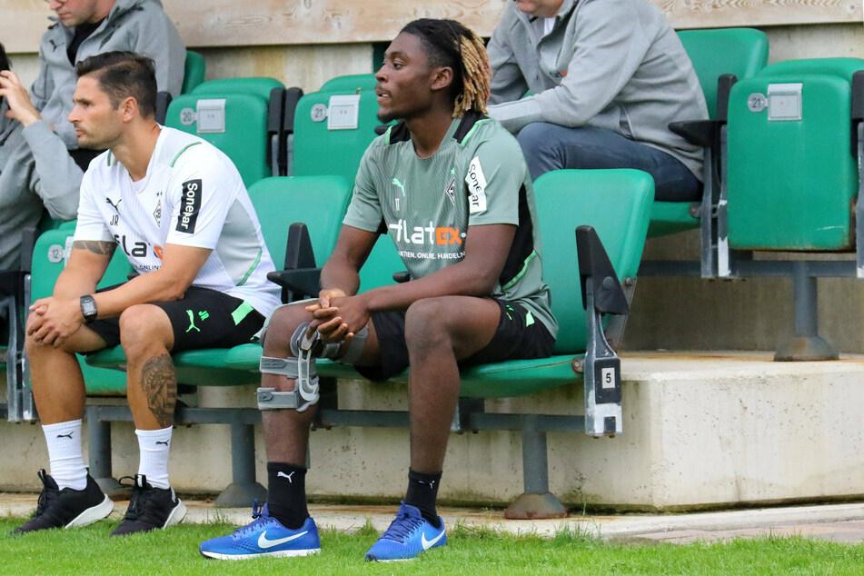 Der verletzte Kouadio Manu Koné (20) darf beim Training nur zuschauen. Hier sitzt er neben Athletiktrainer Jonas Rath (41, l.).