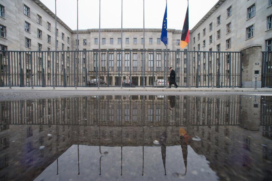 Ein Mann geht in Berlin am Bundesfinanzministerium vorbei, das sich in einer Regenpfütze spiegelt.