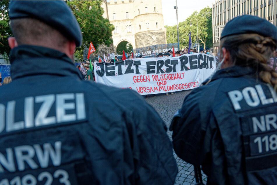 """Teilnehmer einer Spontandemonstration in Köln halten ein Plakat mit der Aufschrift: """"Jetzt erst recht, gegen Polizeigewalt und Versammlungsgesetz""""."""