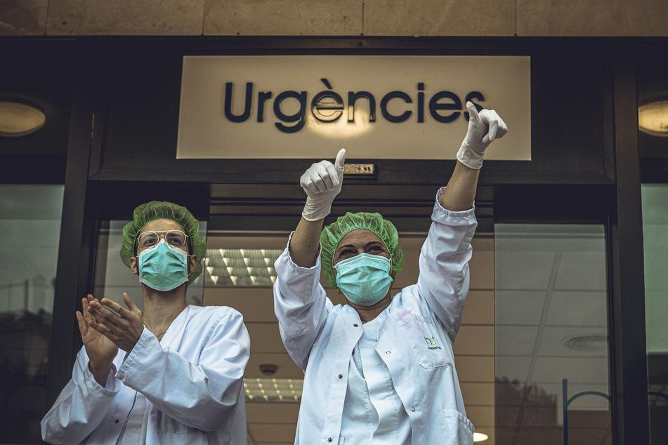 Mitglieder des Gesundheitspersonals der Klinik Plato klatschen und freuen sich über den Applaus, den Anwohner ihnen zur Unterstützung ihrer Arbeit im Kampf gegen das Coronavirus widmen.