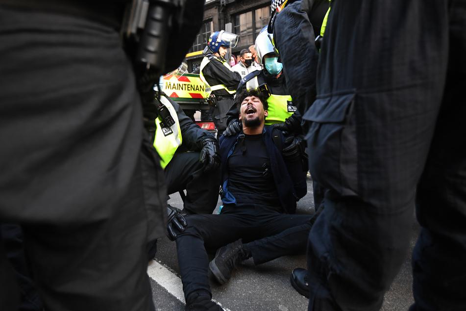 Die Polizei verhaftet einen Mann während einer Demonstration gegen die Corona-Beschränkungen.
