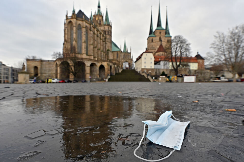 Ein Mund-Nasen-Schutz liegt auf dem Domplatz in Erfurt in einer Pfütze. Thüringen hat derzeit bundesweit die niedrigste Inzidenz.
