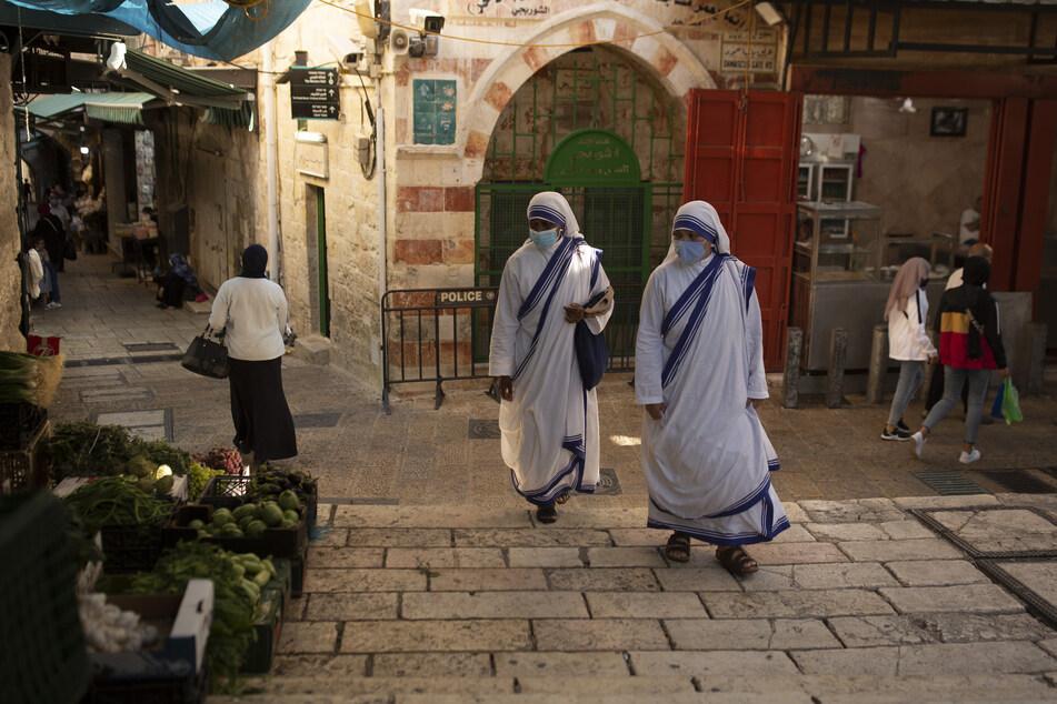 Katholische Nonnen gehen mit Mund-Nasen-Schutz über einen Platz in der Altstadt von Jerusalem.