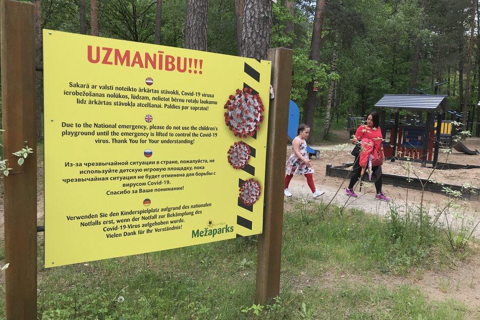 Ein Hinweisschild steht neben einem Spielplatz im beliebten Naherholungsgebiets Mezaparks in der lettischen Hauptstadt Riga.