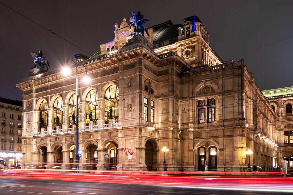Die Lichter vorbeifahrender Autos sind vor der Wiener Staatsoper am Abend zu sehen.