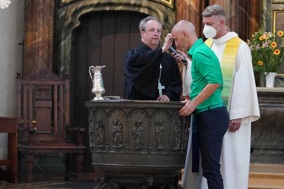 Bischof Christian Stäblein (52) tauft den Ex-Fußballprofi Marcus Urban (50) beim Gottesdienst am Vorabend des Christopher Street Days.