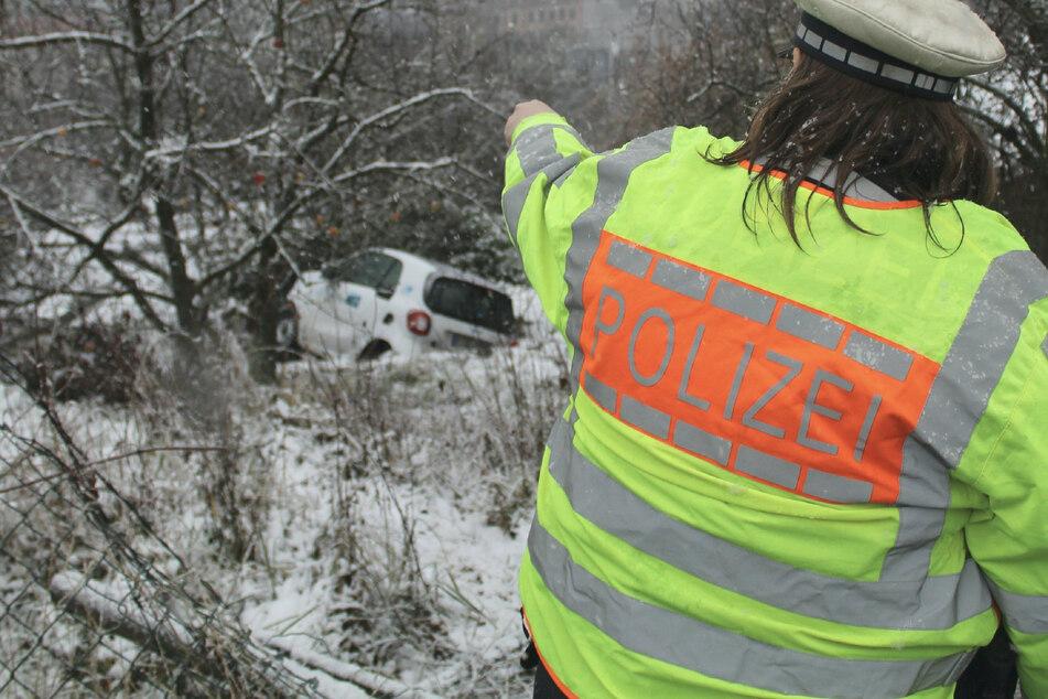 Eine Polizistin zeigt auf den Unfallwagen.