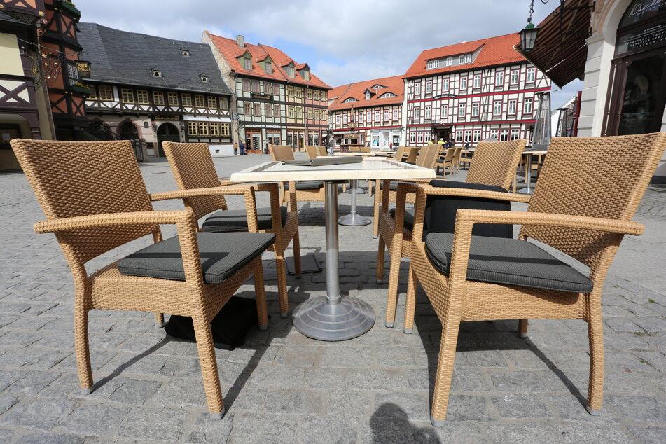 Auf dem Marktplatz stehen leere Tische und Stühle vor einem Café.