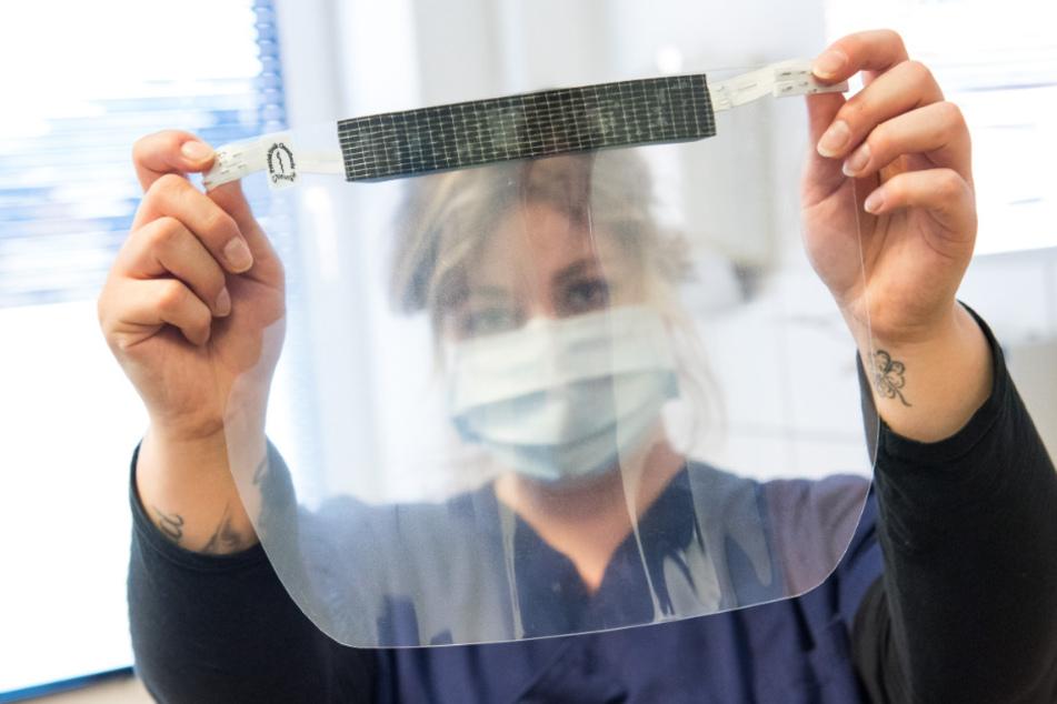 Jana Cords, medizinische Fachangestellte, hält einen selbst gefertigten Gesichtsschutz hoch.