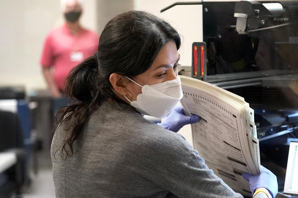 Eine Wahlhelferin hält Stimmzettel im Bezirksbüro Maricopa County Recorders Office zur Auszählung in der Hand.