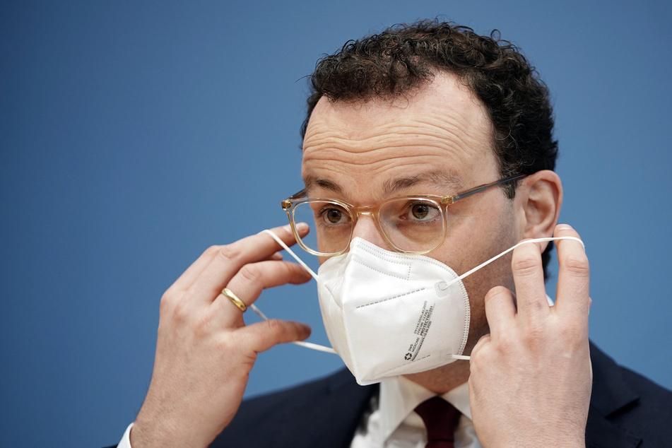 Jens Spahn (40, CDU), Bundesminister für Gesundheit, zieht seinen Mund-Nasen-Schutz bei einer Pressekonferenz zur aktuellen Lage in der Corona-Pandemie in der Bundespressekonferenz auf.