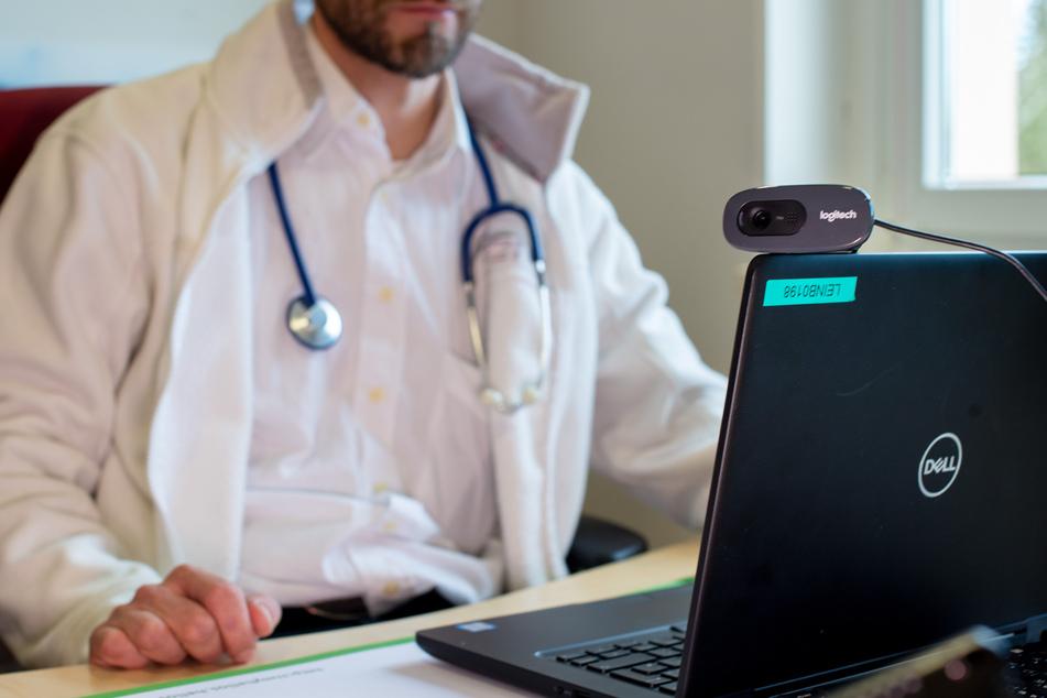 Ein Hausarzt spricht während einer Videosprechstunde in seiner Praxis mit einer Patientin.