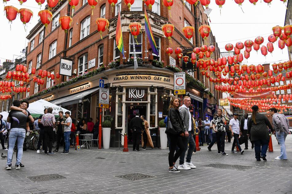 Menschen sitzen und trinken vor einem Pub im Stadtteil Soho. Nach mehr als drei Monaten Schließung wegen der Corona-Pandemie haben die Pubs in England wieder geöffnet.