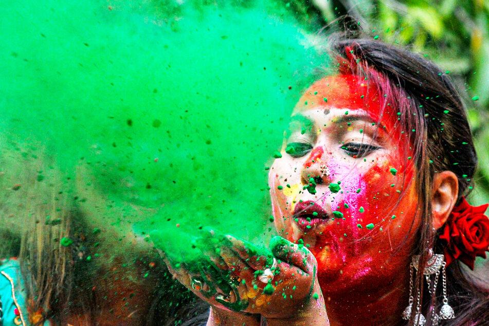Eine geschminkte Studentin pustet farbiges Pulver von ihren Händen während der Holi-Feierlichkeiten an der Universität Kalkutta, Indien.
