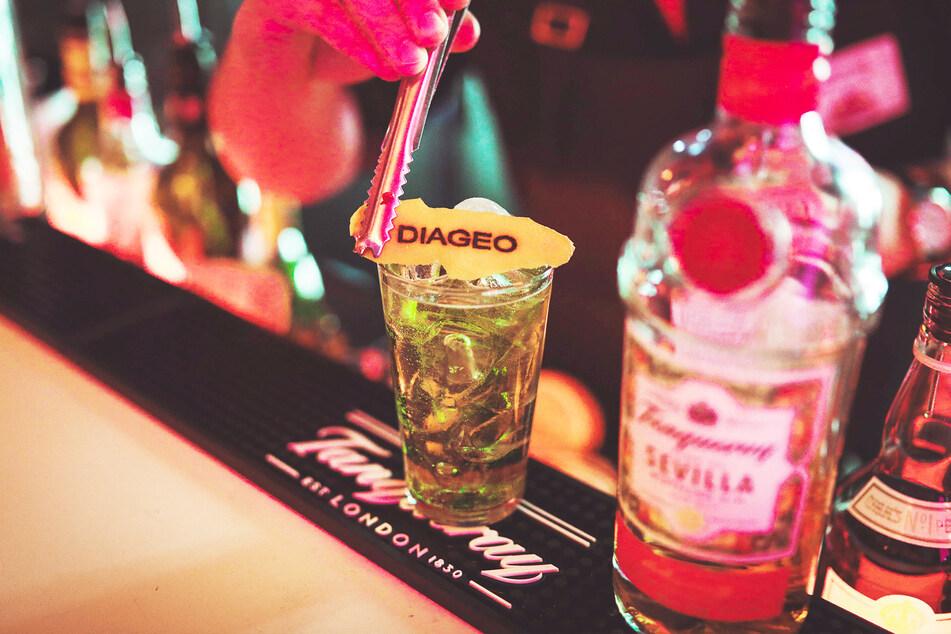 """Ein Barkeeper mixt einen Tanqueray-Gin mit Tonic und richtet das Getränk mit einem Stück Zitronenschale an, auf dem """"Diageo"""" steht."""