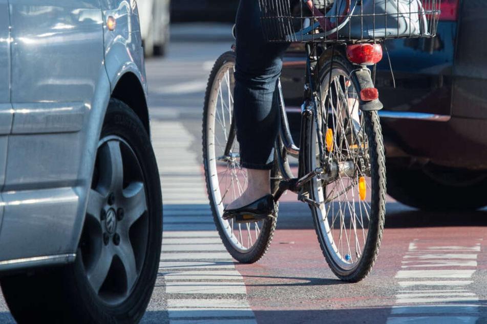 Typische Gefahrensituation: Eine Fahrradfahrerin radelt auf einem Radweg, während Autos rechts abbiegen. (Symbolbild)