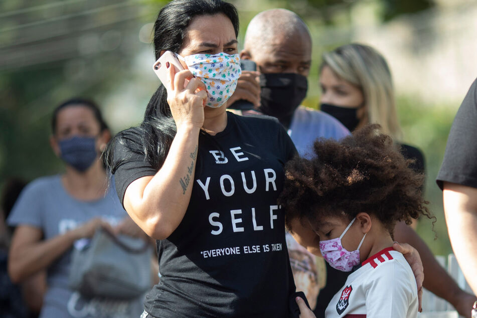 Brasilien, Rio De Janeiro: Menschen mit Mundschutzmasken warten in Duque de Caixas darauf, auf Covid-19 getestet zu werden.