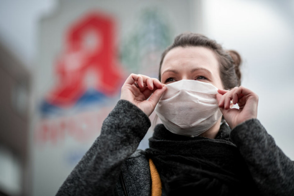 Eine Frau mit Mundschutz. In Schleswig-Holstein gibt es bislang keine bestätigten Viren-Fäle. (Symbolbild)
