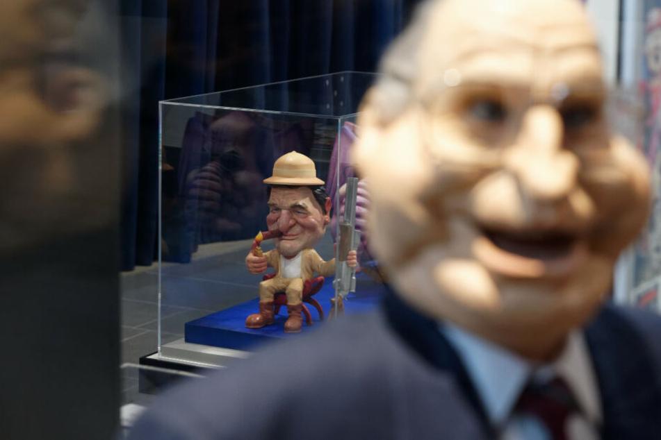 Die Karikatur von Gerhard Schröder in einem Glaskasten.