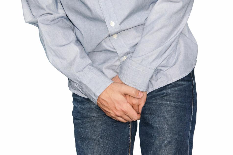 Mann hält sich schmerzerfüllt die Hände vor den Schritt. (Symbolbild)