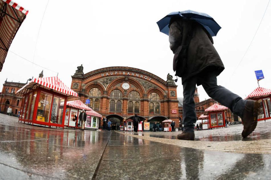 Ein Mann geht bei regnerischem Wetter mit einem Regenschirm in Richtung Hauptbahnhof Bremen.